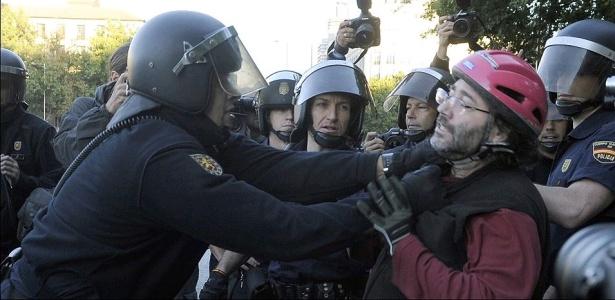 Policial (esq.) ataca ciclista diante da estação de trem Atocha, em Madri, durante greve geral contra reforma trabalhista do governo espanhol