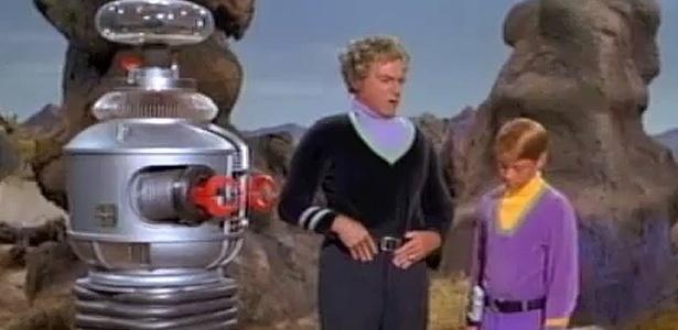 """Robô, dr. Smith e Will Robinson, em cena da série de ficção científica """"Perdidos no Espaço"""""""