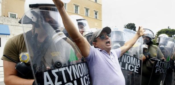 Manifestante protesta diante de grupo de policiais durante paralisação em Atenas, Grécia