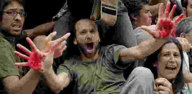 Homem mostra as mãos cobertas de sangue durante manifestação em Barcelona contra a crise econômica - Josep Lago/AFP