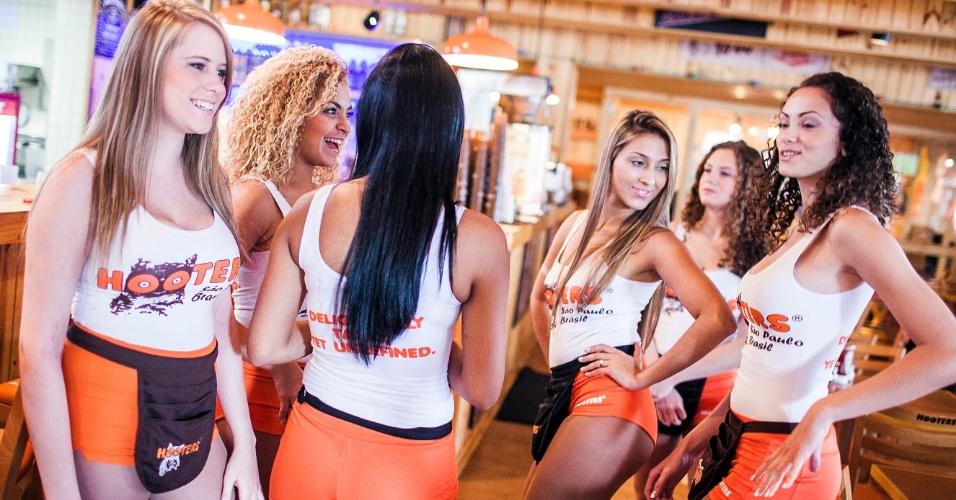 Garçonetes da rede de fast-food Hooters participam de treinamento; elas aprendem a fugir de cantadas, fazer maquiagem, andar de patins, entre outras funções