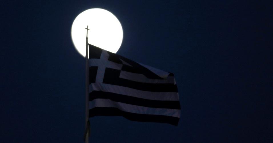 Bandeira grega é vista em frente à lua em Atenas